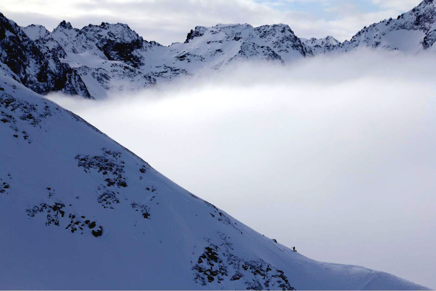 Lone skier above clouds © JonoVernon-Powell